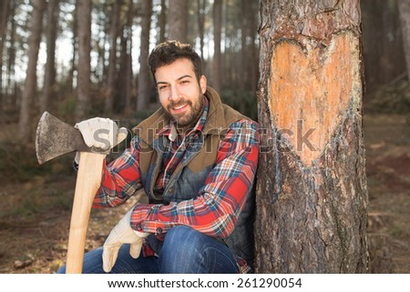Portrait of an attractive young lumberjack man in love, carved a heart symbol in the tree with his axe - stock photo
