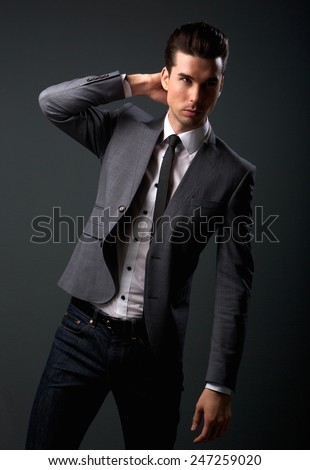 Portrait of an attractive young male fashion model in suit jacket and tie - stock photo