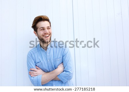 Portrait of an attractive young man laughing with arms crossed  - stock photo