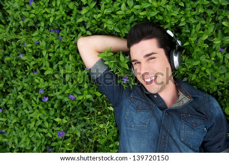 Portrait of an attractive young man lying on grass listening to music on headphones - stock photo