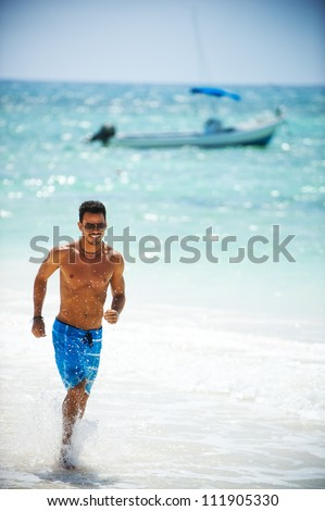 Portrait of an attractive young man on a tropical beach - stock photo