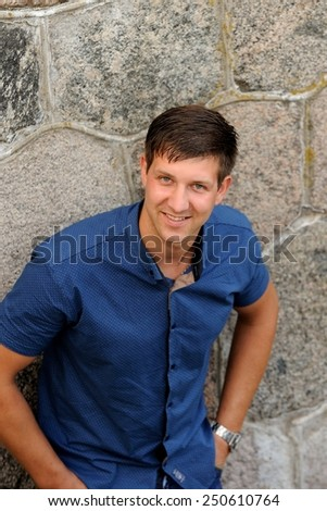 Portrait of an attractive young man standing next to a stone wall.