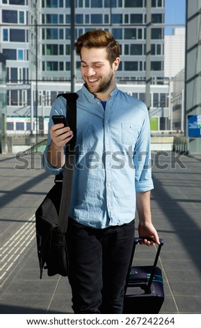 Portrait of an attractive young man walking at airport with bags and mobile phone - stock photo