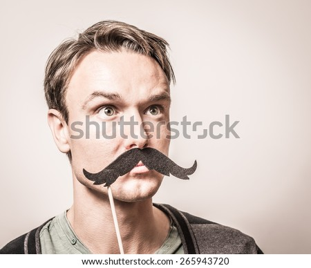 Portrait of an attractive young man wearing a giant retro style fake mustache. - stock photo