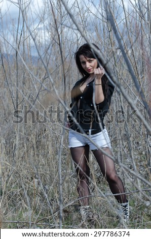 Portrait of an attractive young model standing at the dry trees without leaves in a opened hooded coat and a black bra