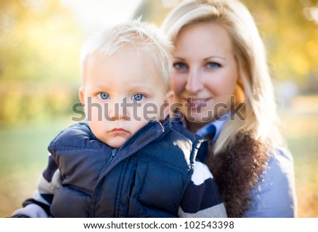 Portrait of an attractive young mother with her son in the park. - stock photo