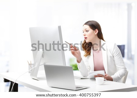 Portrait of an attractive young office worker sitting at her desk and working on a computer and laptop.