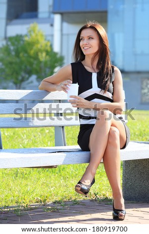 Portrait of an attractive young professional woman drinking coffee from disposable paper cup while sitting on a wooden bench in a park, smiling.  - stock photo