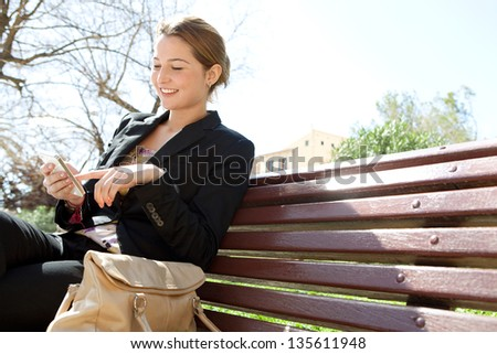 Portrait of an attractive young professional woman using a smartphone while sitting on a wooden bench in a city park, smiling. - stock photo