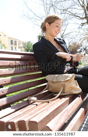 Portrait of an attractive young professional woman using a smartphone while sitting on a wooden bench in a city park, smiling.