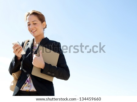 Portrait of an attractive young professional woman using a smartphone while standing against a sunny blue sky, smiling. - stock photo