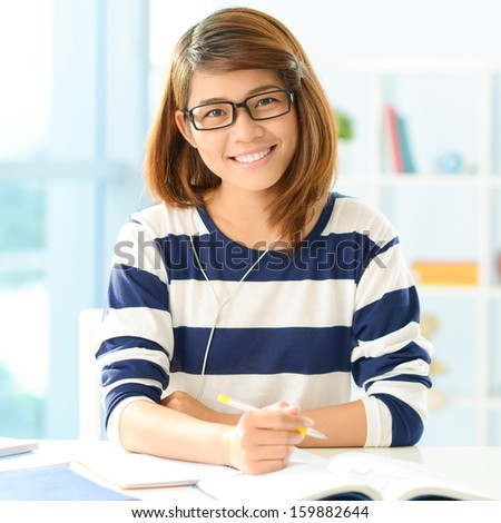 Portrait of an attractive young student doing her homework at home - stock photo