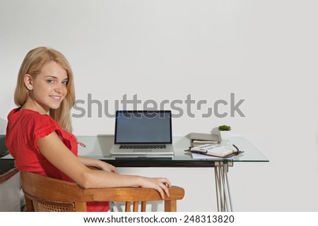 Portrait of an attractive young student using laptop technology at home to study and do her homework, sitting at her home desk with a computer and paperwork. Young professional smiling indoors. - stock photo