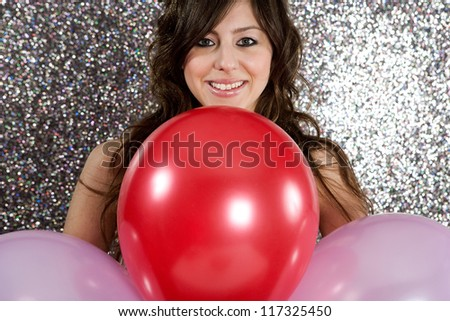 Portrait of an attractive young woman against a silver glitter background, holding three balloons in red and pink, smiling.
