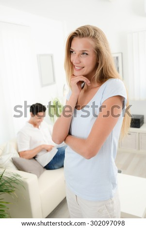 portrait of an attractive young woman at home with boyfriend in background - stock photo