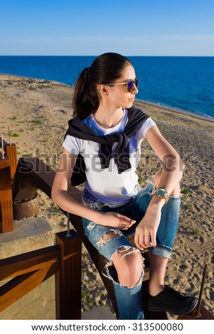 Portrait of an attractive young woman dressed in stylish clothes resting after active walk along the seashore, trendy female sitting on the beach against sea enjoying vacation holidays in spring - stock photo