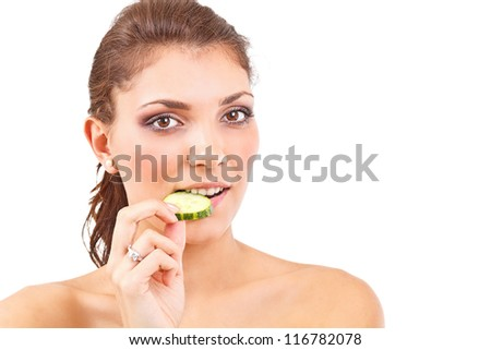 Portrait of an attractive young woman eating a slice of cucumber - stock photo