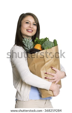 Portrait of an attractive young woman holding a bag of groceries