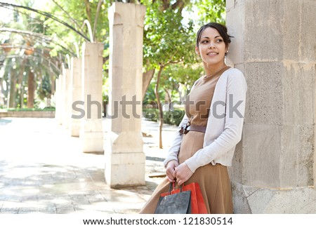 Portrait of an attractive young woman holding her shopping bags while leaning on a stone column in a romantic garden, being thoughtful outdoors. - stock photo