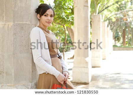 Portrait of an attractive young woman holding her shopping bags while leaning on a stone column in a romantic garden, outdoors. - stock photo