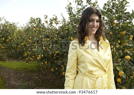 Portrait of an attractive young woman in an lemon grove. - stock photo