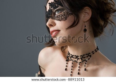 Portrait of an attractive young woman in elegant lace mask and accessories