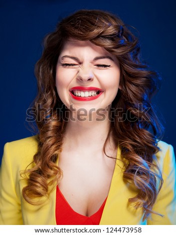 Portrait of an attractive young woman laughing hard - stock photo