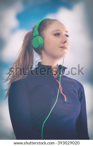 Portrait of an attractive young woman listening to music in green headphones against blue skies. Warm filter applied