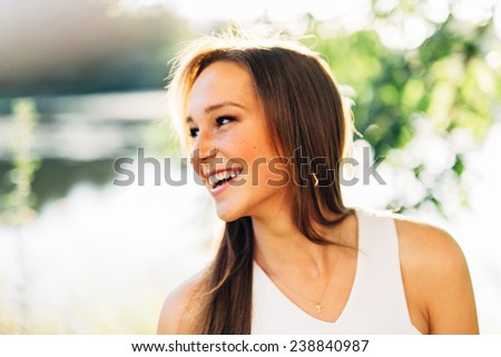 Portrait of an Attractive Young Woman Looking off to side smiling and laughing close up