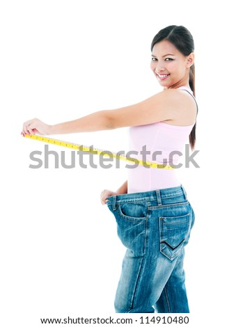 Portrait of an attractive young woman measuring her waist after losing weight over white background. - stock photo