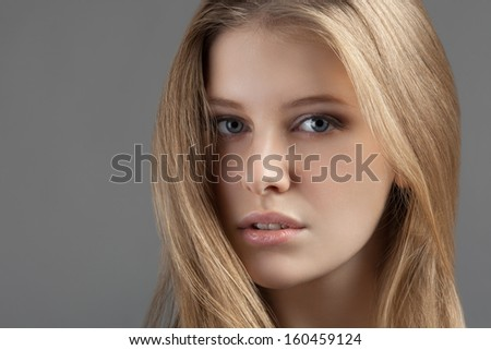 Portrait of an attractive young woman on a gray background - stock photo