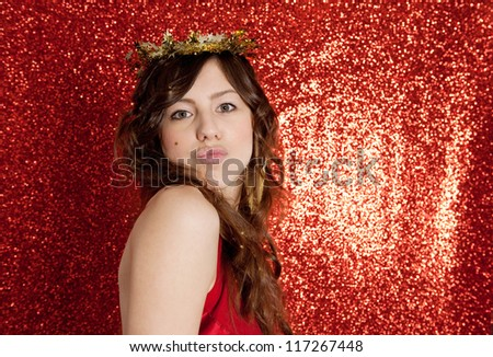 Portrait of an attractive young woman sending a kiss and wearing a gold stars crown while standing in front of a Christmas red glitter background.