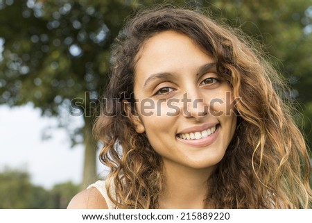 Portrait of an attractive young woman smiling to camera whilst outdoors on a warm day - stock photo