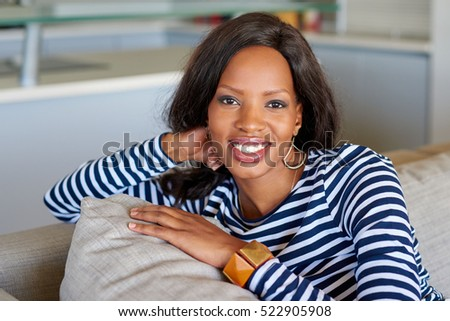Portrait of an attractive young woman smiling while relaxing on a sofa at home