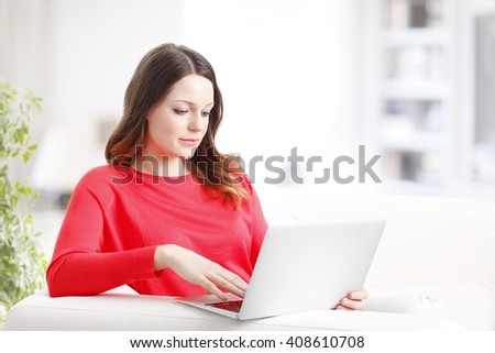 Portrait of an attractive young woman using laptop while sitting at couch and relaxing.  - stock photo