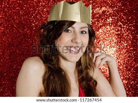 Portrait of an attractive young woman wearing a gold paper crown while standing in front of a Christmas red glitter background. - stock photo
