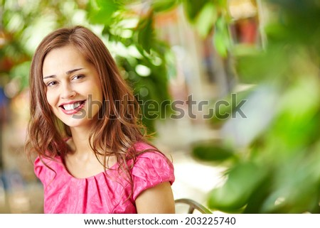 Portrait of an attractive young woman with a charming smile wearing fuchsia pink