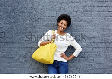 Portrait of an attractive young woman with handbag standing against a gray wall - stock photo