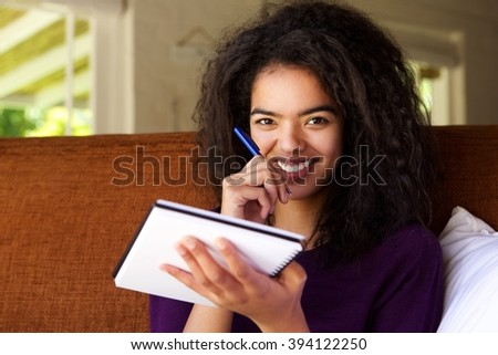 Portrait of an attractive young woman writing ideas in book - stock photo