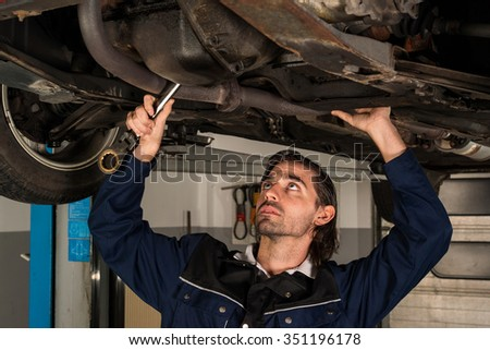 Portrait of an auto mechanic working underneath a lifted car - stock photo