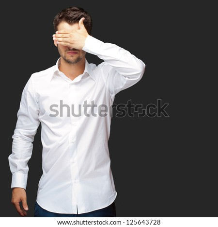 Portrait Of An Businessman Covering Eyes Isolated On Black Background