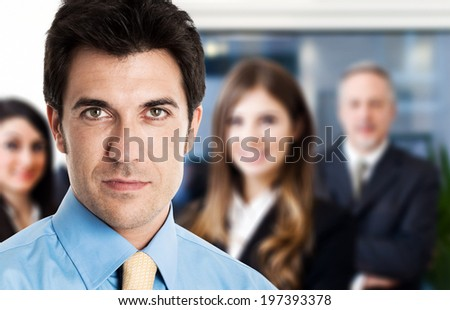 Portrait of an businessman in front of his team - stock photo
