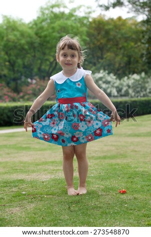 Portrait of an cheerful little girl in blue dress. Vertical photo - stock photo