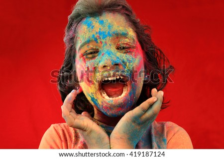 Portrait of an cheering Indian girl with face smeared with colours in a red background. Concept for Indian festival Holi. - stock photo