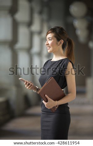 Portrait of an Chinese businesswoman standing outside using her smart phone. - stock photo