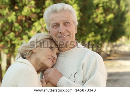 Portrait of an elderly couple on the background of the autumn landscape