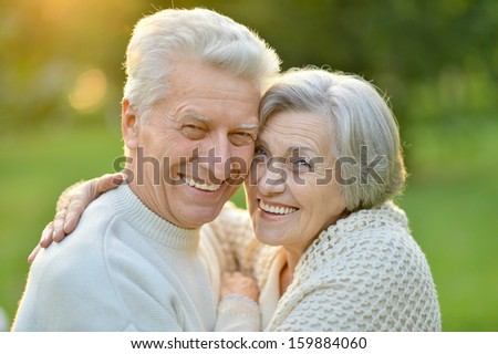 Portrait of an elderly couple on the background of the autumn landscape - stock photo