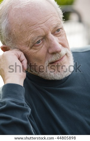 Portrait of an Elderly Gentleman Sitting on a Bench in a Park - stock photo