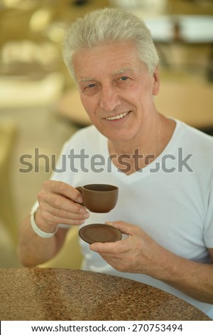 Portrait of an elderly man drinking cup of coffee