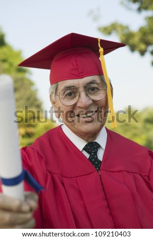 Portrait of an elderly man in graduation attire holding degree